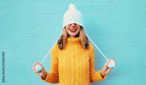 Portret zimowy szczęśliwy uśmiechnięta młoda kobieta zabawy ciągnie kapelusz na oczy, ubrany w żółty sweter z dzianiny i biały kapelusz z pom pom na niebieskim tle ściany