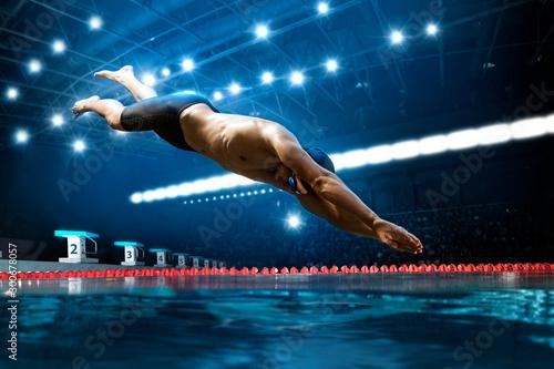 Obraz na płótnie Swimmer jumping from starting block in a swimming pool