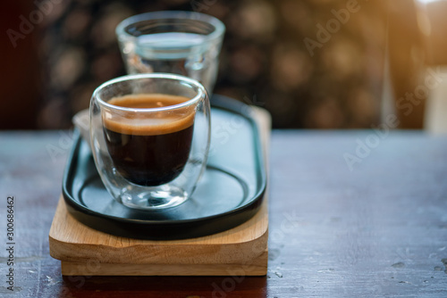Fotografia Hot espresso coffee in a clear glass, placed on a metal tray and wooden layer beside the coffee cup with a bear shaped cookie