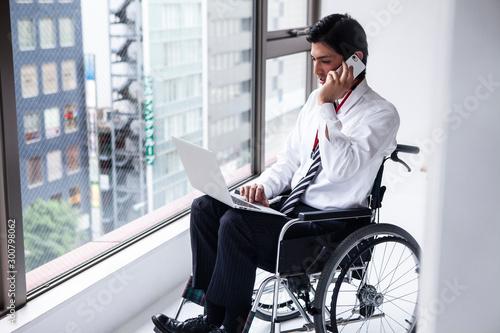 Photo 電話をかける車椅子のビジネスマン