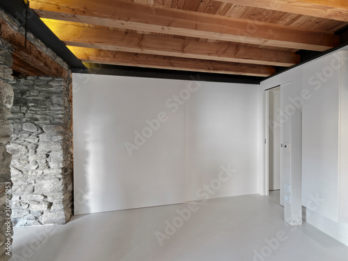 Photo a empty room with wooden ceiling and concrete floor whose walls are of stones