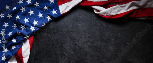 US American flag on worn black background. For USA Memorial day, Veteran's day, Labor day, or 4th of July celebration. With blank space for text.