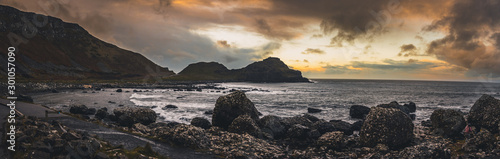 Foto Panoramic view of the pathways and the bay at the coast called Giant's Causeway, a landmark in Northern Ireland, with the cliffs that surround the place and dramatic cloudy sky