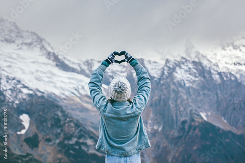 Платно Young traveler girl in gloves standing over mountain peaks and making heart by h