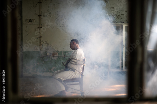 Fotografia A crazy man in a straitjacket is tied to a chair in an abandoned old clinic