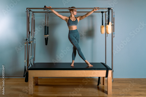 Valokuvatapetti Pilates woman in a Cadillac reformer doing stretching exercises in the gym
