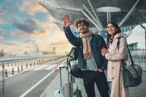 Canvas Print Young man and woman stand outside airport and wait for taxi cab