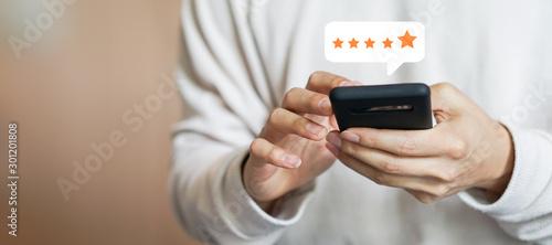Obraz na płótnie close up on customer man hand pressing on smartphone screen with gold five star