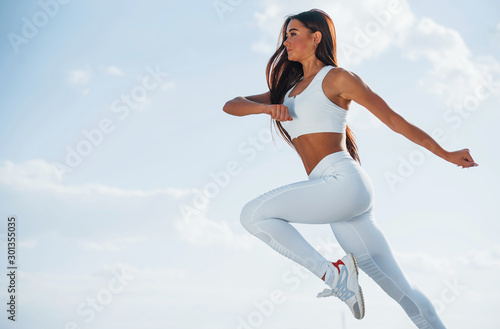 Up in the sky. Female runner in white sportive clothes doing fitness