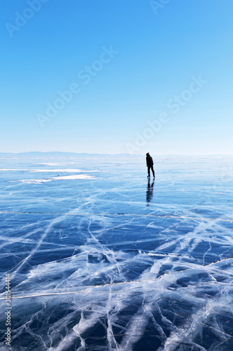 Frozen Baikal Lake in February. The endless desert of blue ice with a crack. A lone tourist skates on ice in the distance. Winter landscape. Natural background
