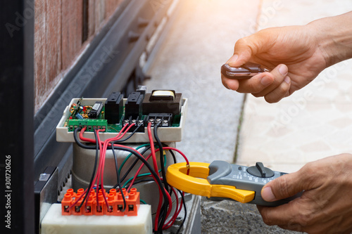 Technician man hand pressing remote control while repair and using digital clamp Fototapete