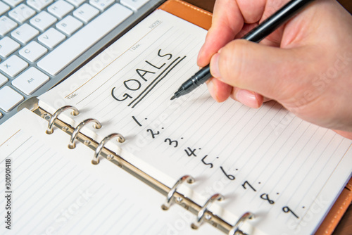 Close-up of a businessman's hand writing goals and list in the diary Fototapeta