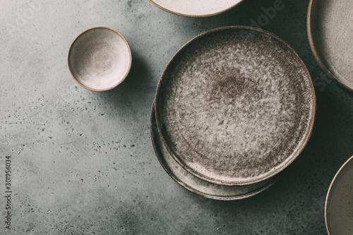 Murais de parede Empty ceramic bowls and plates on a dark background