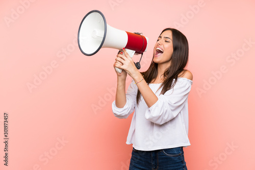 Young woman over isolated pink background shouting through a megaphone Tapéta, Fotótapéta