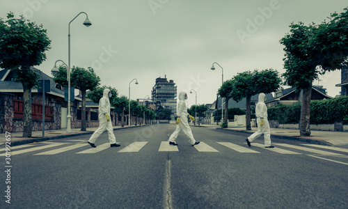 Photographie People with bacteriological protection suits crossing a crosswalk in a row