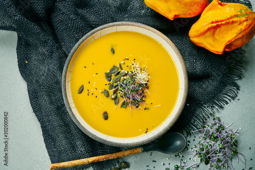 Canvas Print Fresh vegetarian pumpkin cream-soup with mushrooms and teriyaki sauce on a gray fabric in a composition with ginger