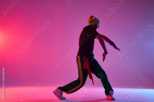 Canvas Print Handsome young professional hip hop dancer performing on stage of dance school,