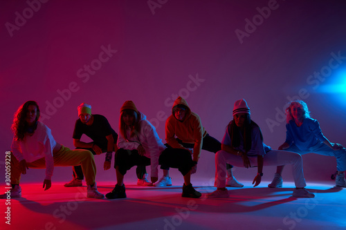 Canvas Print Big group of young people sitting on squat on dark lighted stage, waiting for be