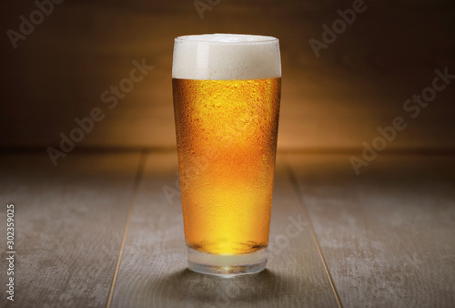 Fototapeta Beautiful colorful glass of IPA beer served on retro wooden surface, ale, golden