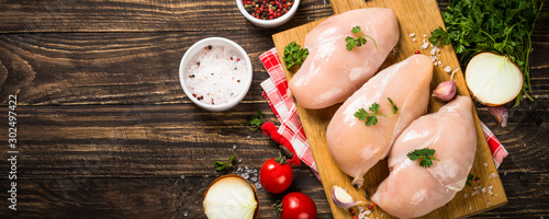 Fotografia Chicken fillet with ingredient on wooden table.