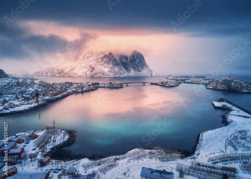 Fotografía Aerial view of snowy mountain, village on sea coast, orange sky at sunset in winter