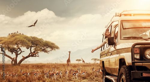 Fotografia Happy woman traveller on a safari in Africa, travels by car in Kenya and Tanzania, watches life wild tigers, giraffes, zebras and antelopes in the savannah