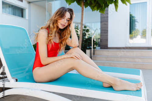 Photo of woman looking at camera while sitting on chaise lounge Fototapeta