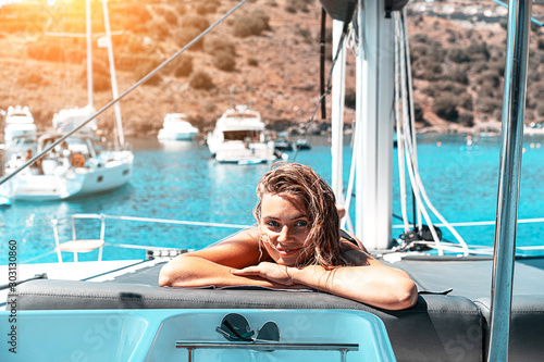Leinwand Poster Young happy woman feels fun on the luxury sail boat yacht catamaran in turquoise sea in summer holidays
