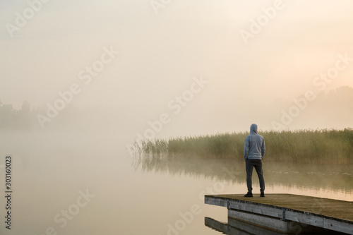 Canvas Print Young man standing alone on wooden footbridge and staring at lake
