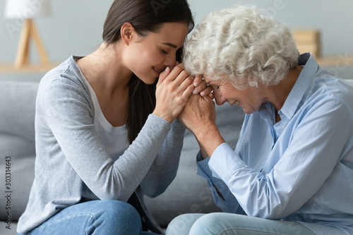 Photo Caring young adult woman granddaughter hold hands of old grandmother