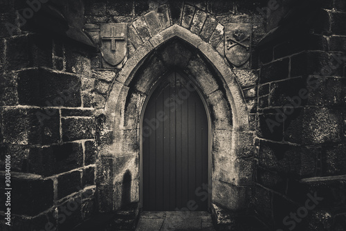Scary pointy wooden door in an old and wet stone wall building with cross, skull and bones at both sides in black and white. Concept mystery, death and danger.