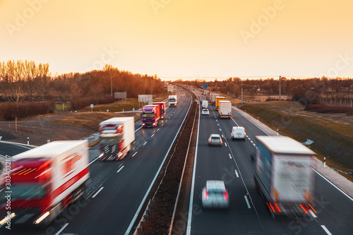 Fototapeta Busy highway with fast moving vehicles in beautiful sunset