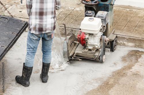 Fotografie, Tablou Worker using diamond saw blade machine cutting concrete road at construction sit