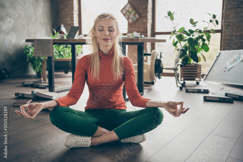 Work anti-stress concept. Full size photo of dreamy ceo worker woman have much job problems sit floor try calm practice yoga exercise meditate in messy big company office