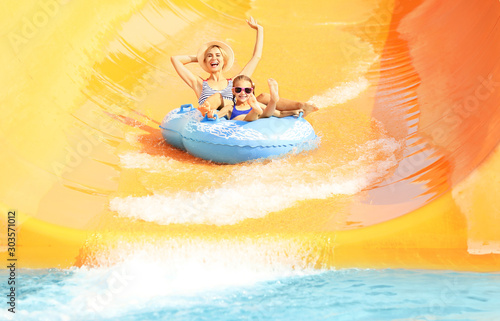 Little girl and her mother having fun in aqua park Poster Mural XXL