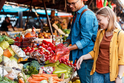Canvas Print Beautiful young couple buying fresh vegetables on outdoor market.