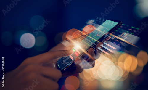 Billede på lærred Stock exchange market concept, hand trader touching on smartphone with graphs analysis candle line on bokeh colors light in night atmospheric city