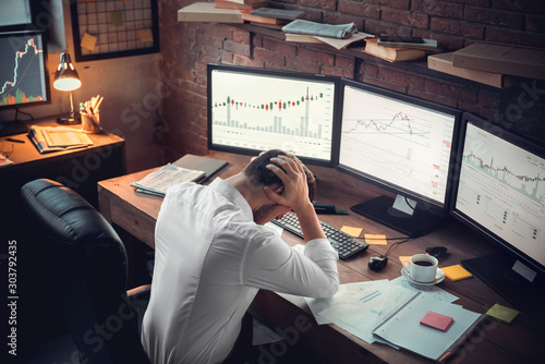 Young male trader at office work concept hard-working person Fototapet