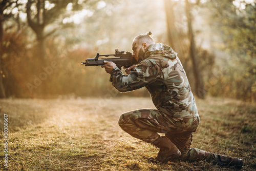 A camouflage soldier playing airsoft outdoors in the forest, standing on one kne Fototapet