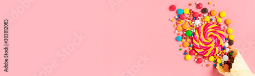 mix colorful chocolate sweets spilled out of ice cream waffle cone on pink background Flat lay Top view Place for text Holiday card Happy birthday party, Happy Valentine's day concept banner