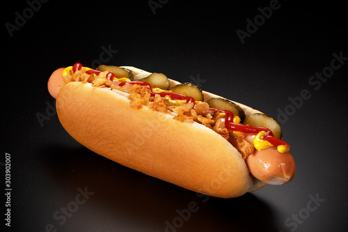 Fotografie, Obraz Danish hot dog with pickled cucumbers, fried onions, ketchup and mustard on a black background