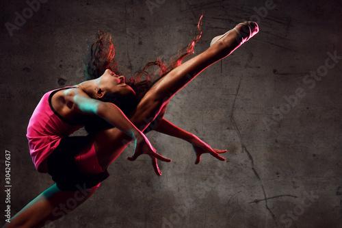 Canvas-taulu Street dance girl dancer jumping up dancing in neon light doing gymnastic exerci