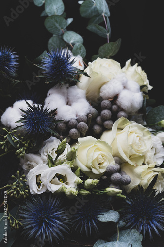 Winter wedding bouquet of white roses, cotton and eringium on a black background. The bride's bouquet.