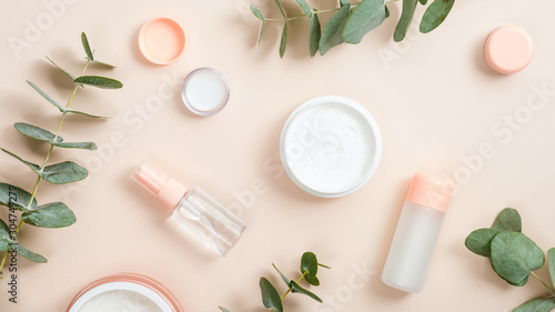 Flat lay composition with natural organic cosmetic products on beige background. Top view hand cream in jar, essential oil, skin lotion and eucalyptus leaves. Natural organic beauty product concept