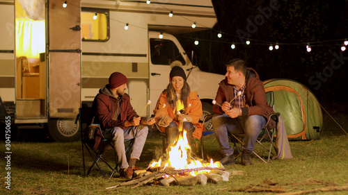 Fotografiet Group of happy friends around burning camping fire