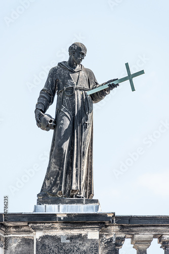 Fotografia, Obraz Very old roof statute of high ranked priest with a cross and human skull in hist