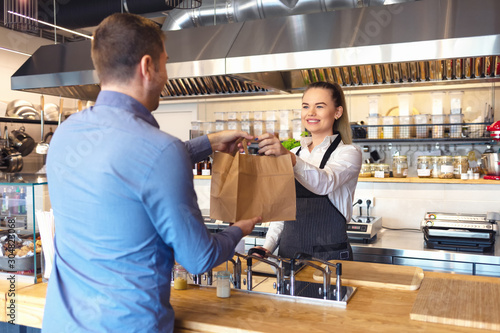 Obraz na plátně Happy waitress wearing apron serving takeaway food to customer at counter in small family restaurant
