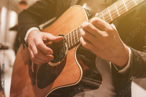 Fotografie, Tablou Acoustic guitar playing. A man playing an acoustic guitar.