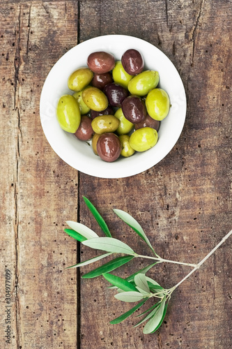 Fototapeta Black and green olives in a small bowl on a rustic wooden background Italian ape