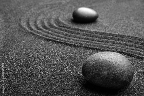 Black sand with stones and beautiful pattern. Zen concept